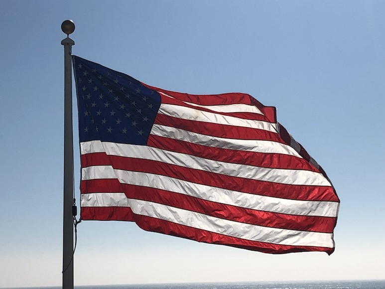 Photo of an American flag on a flagpole against a blue sky