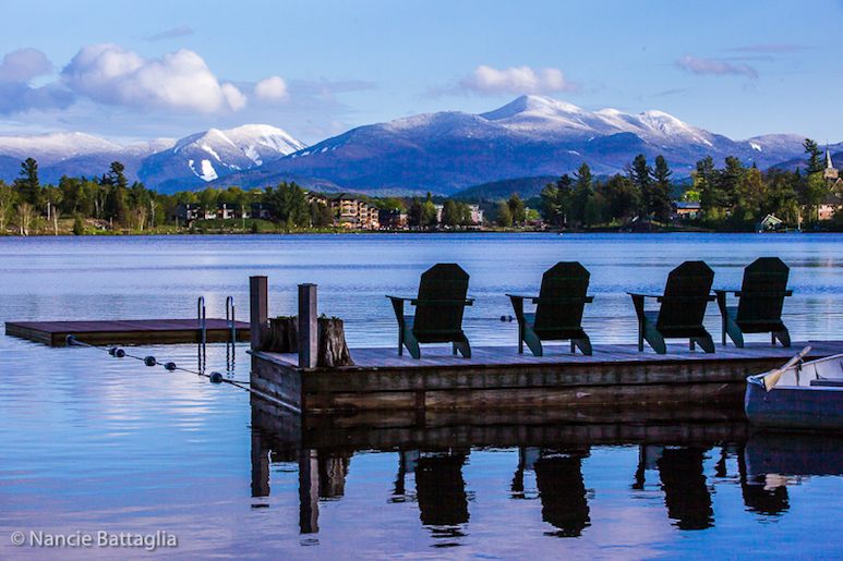 View of Adirondack chairs on a dock looking out on a lake and snow-capped mountains beyond