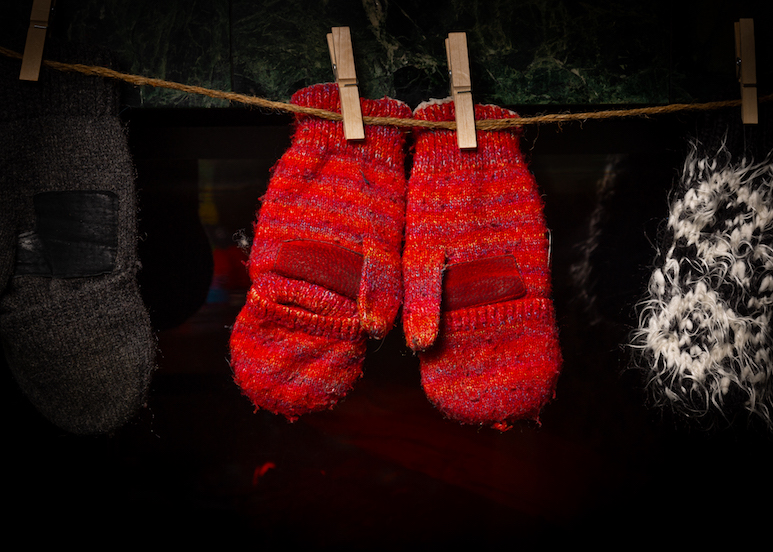 A pair of red wool mittens hanging from a line