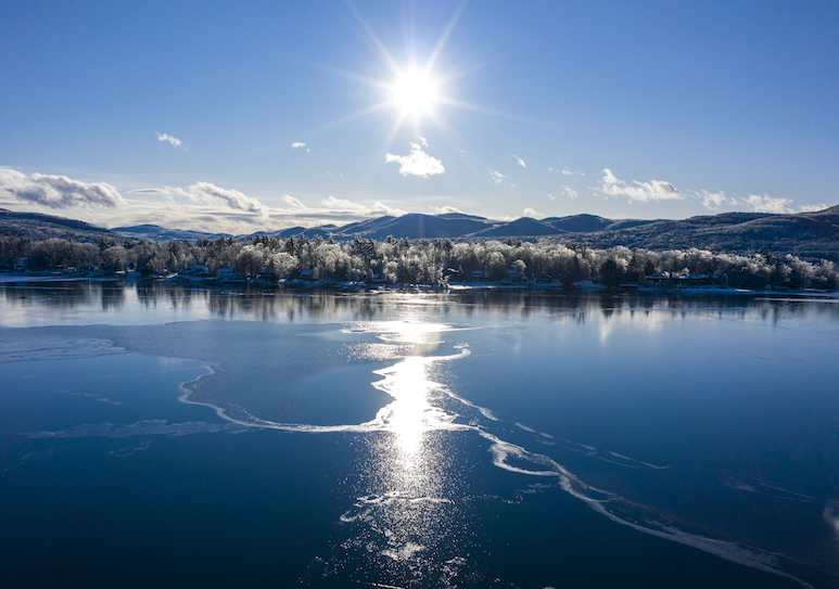 Winter landscape scene with bright sun looking over a lake at the mountains with snow