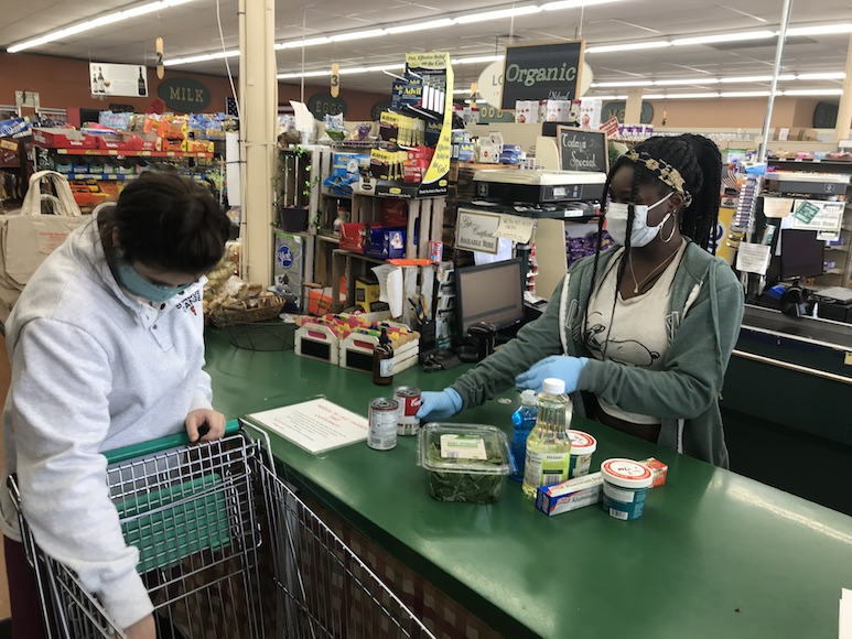 A grocery store cashier checking out a customer, both wearing masks