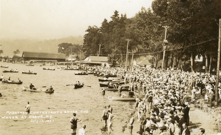 Historic photo of a crowd of swimmers along a lakeshore ready to begin a swim race