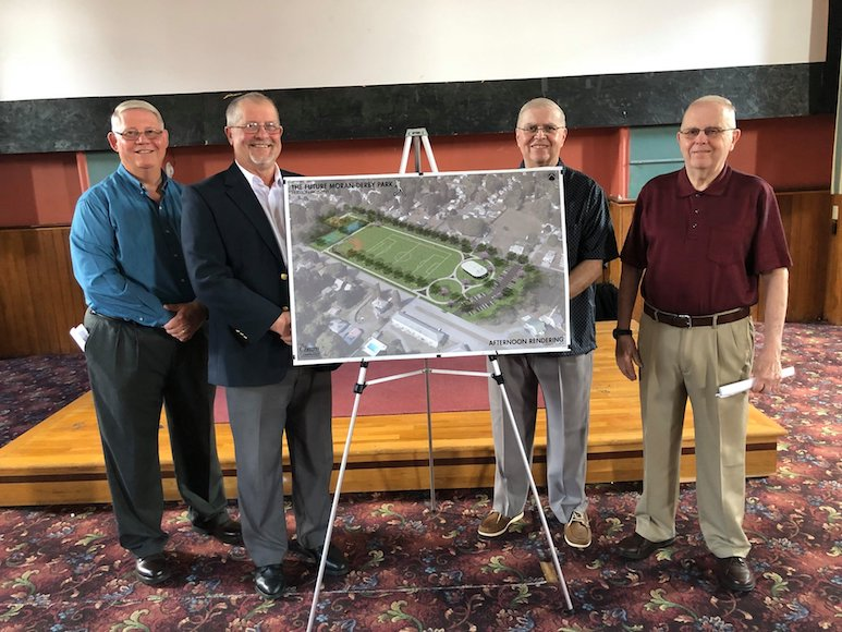 Photo of Hudson Falls village officials and local businessmen, with image of renovations planned at park.