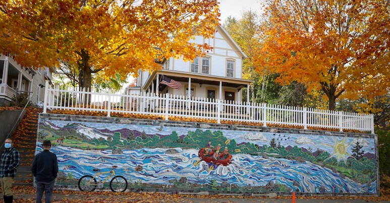 A mural mosaic artwork on wall along a sidewalk, showing a river, people whitewater rafting, a bicycle and mountains.