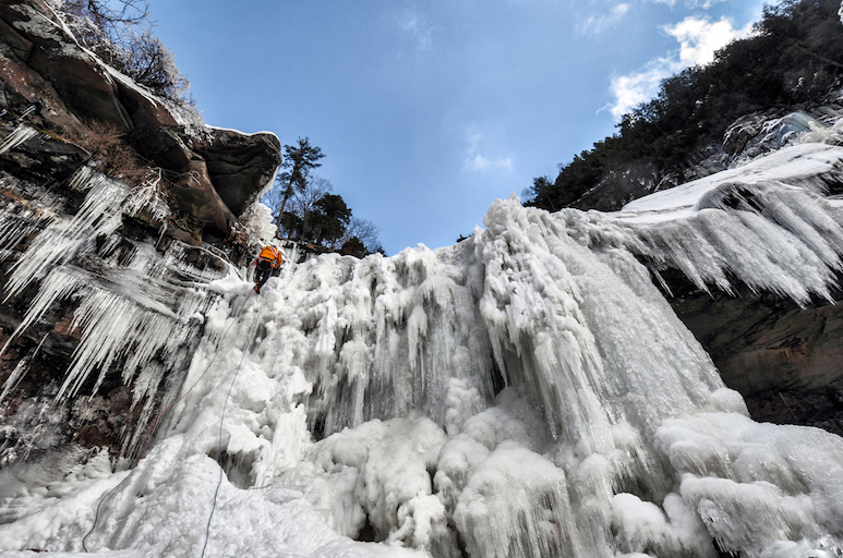 A large frozen waterfall being scaled by an ice-climbing hiker