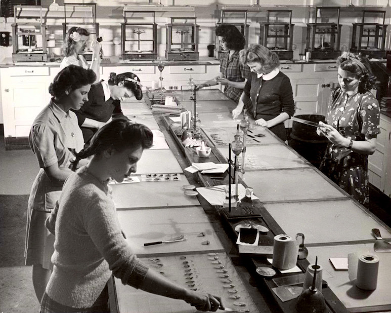 Women at work at a long table in a lab during the 1940s.
