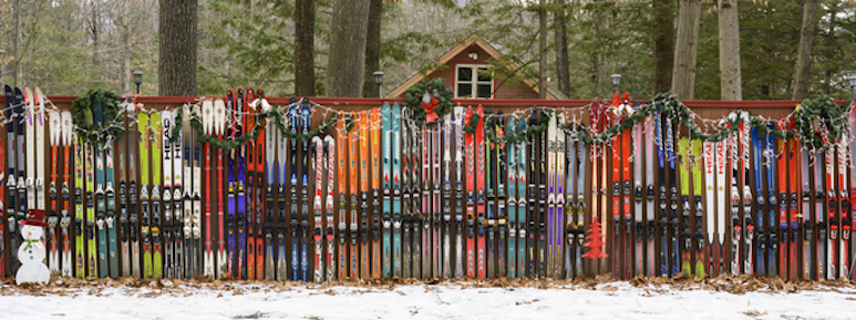 Colorful snow skis lined up along a fence.