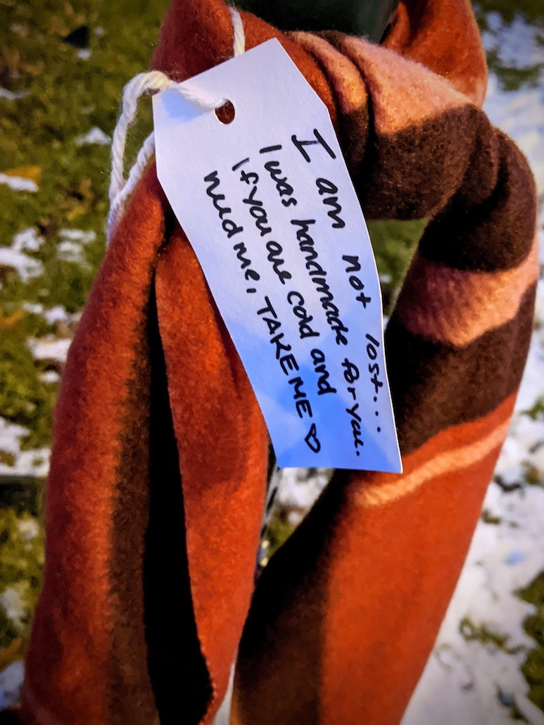 A winter scarf hanging on a park bench with a note reading I am not lost. I was handmade for you. If you are cold and need me, take me.