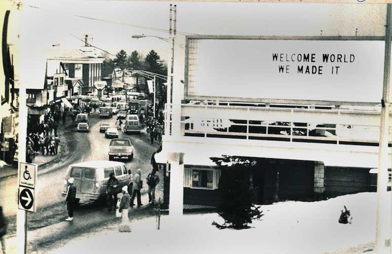 "1980 photo of Lake Placid Village during the Olympics, with billboard sign reading ""Welcome World We Made It"""