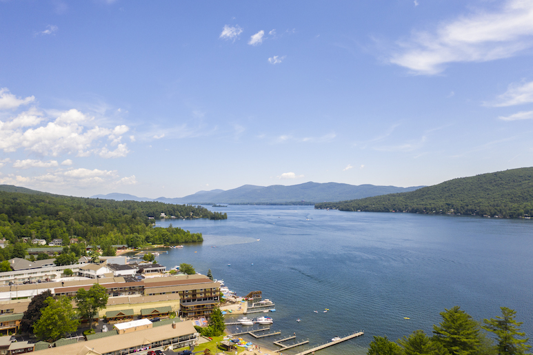 Aerial view of Lake George, with motels on the near shoreline and mountains in the background