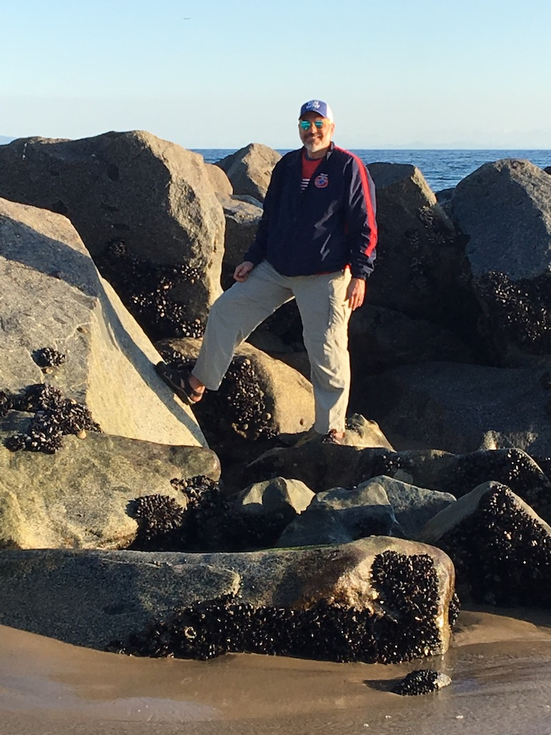 Image of man standing on a rocky shoreline