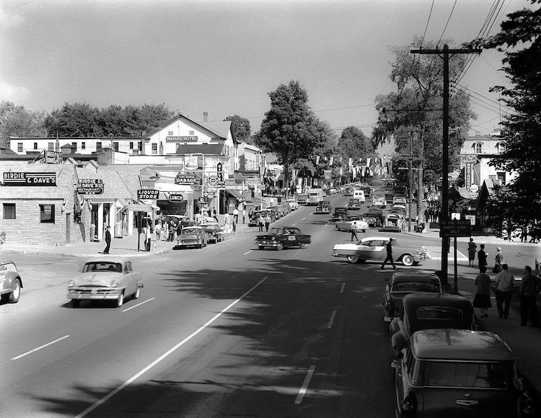 Historic black & white photo of Lake George village with cars and pedestrians