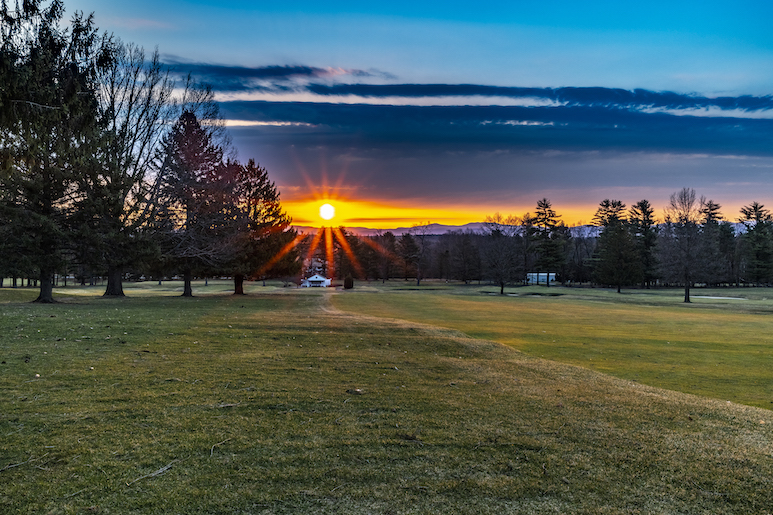 The sun rising over mountains along a golf course.