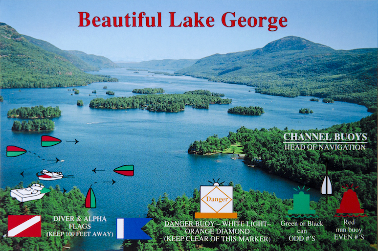 Picture postcard from the 1960s, aerial view of Lake George with islands and mountains in the background and buoy instructions