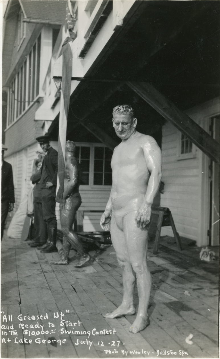 Historic photo of a man greased up and in a bathing suit, ready to enter a lake for a swimming race